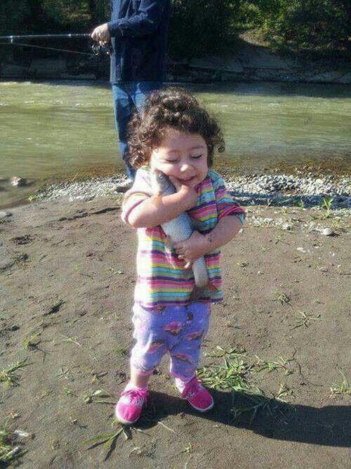 little girl hugging fish
